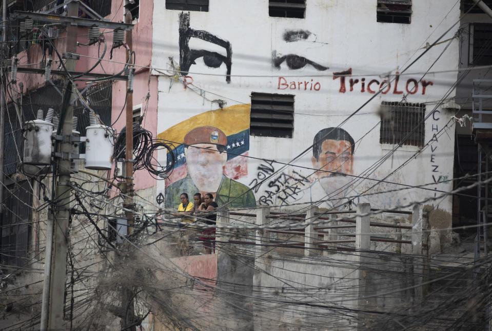 Electricity lines hang in front of a building covered with images of late Venezuelan President Hugo Chavez, left, and current President Nicolas Maduro in the Petare neighborhood of Caracas, Venezuela, Thursday, May 21, 2020. Defying predictions, Venezuela so far seems to have avoided the epidemiological disaster striking much of South America, but experts warn that while the new coronavirus may have been slow to spread here, due in large part to Venezuela's isolation, the number of daily illnesses could soon climb high enough to severely test the country's already dilapidated health system. (AP Photo/Ariana Cubillos)
