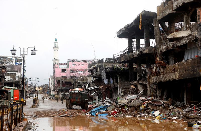 Soldiers walk through a battle damaged street in Marawi City in the Southern Philippines on Oct. 17, 2017.