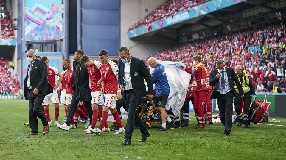 Denmark's Christian Eriksen is surrounded by teammates has he is taken from the field after suffering a cardiac arrest during a match against Finland. (Photo by Lars Ronbog / FrontZoneSport via Getty Images)