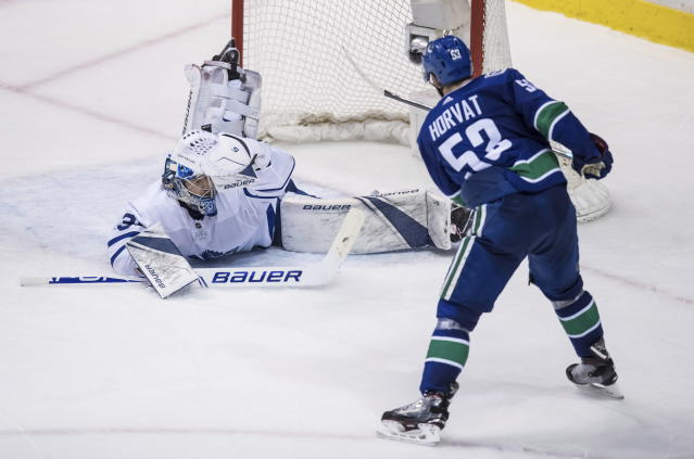 Toronto Maple Leafs goalie Frederik Andersen, left, of Denmark, makes a glove save to stop Vancouver Canucks' Bo Horvat during the second period of an NHL hockey game Wednesday, March 6, 2019, in Vancouver, British Columbia. (Darryl Dyck/The Canadian Press via AP)