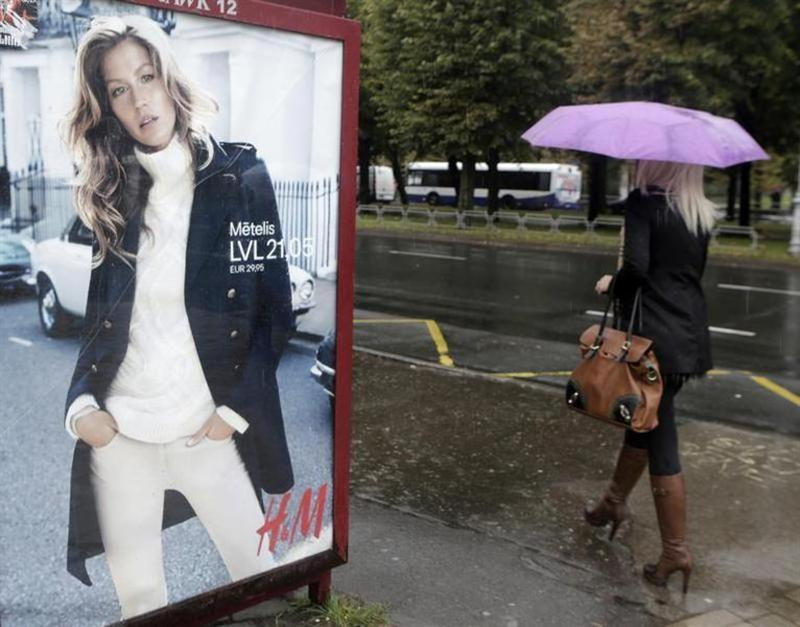 A woman walks past a H&M advertisement in Riga