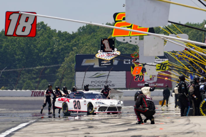 Crew members for Harrison Burton (20) push the car to the pits during a NASCAR Xfinity Series auto race at Pocono Raceway, Sunday, June 27, 2021, in Long Pond, Pa. (AP Photo/Matt Slocum)