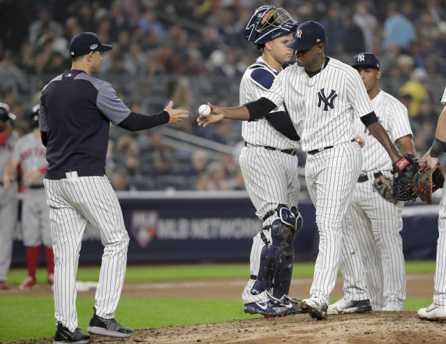 New York Yankees starting pitcher Luis Severino, right, hands the ball to manager Aaron Boone as he leaves the game during the fourth inning of Game 3 of baseball's American League Division Series against the Boston Red Sox, Monday, Oct. 8, 2018, in New York. (AP Photo/Frank Franklin II)