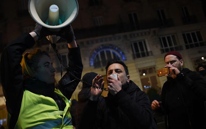 A protester speaks in a megaphone during a demonstration in front of the Bouffes du Nord theatre in Paris - AFP
