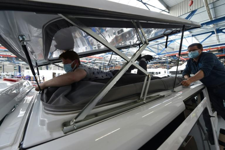 Hundreds of workers pierce and cut into Fiat and Renault vans to add beds, kitchens, bathrooms and sky roofs to the vehicles at a factory of the Pilote company in the western French city of Angers