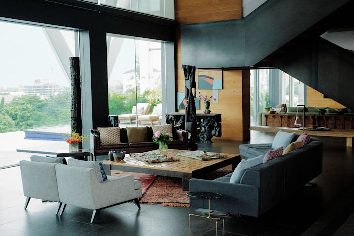 Two carved-wood totems by Nigerian Artist Reuben Ugbine preside over the living room. A pair of Ligne Roset armchairs, A børge Mogensen leather sofa, and a custom Poltrona Frau sofa surround a cocktail table by Jérôme Abel Seguin, who also crafted the mahogany root console at rear. Vintage Moroccan Rug from Nazmiyal Collection.