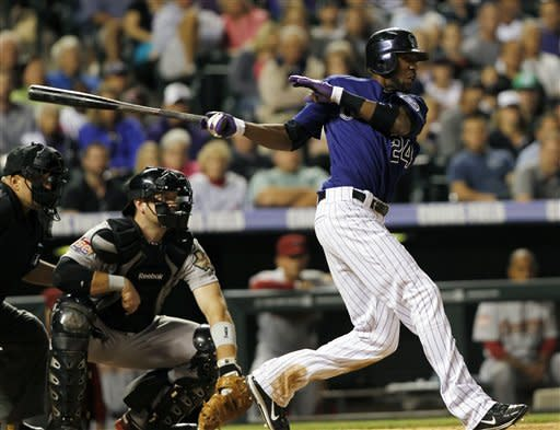 Colorado Rockies' Dexter Fowler, right, follows the flight of his RBI-single to drive in the winning run as Houston Astros catcher Chris Snyder looks on in the 10th inning of the Rockies' 7-6 victory in in game two of a split doubleheader in Denver on Monday, May 28, 2012. (AP Photo/David Zalubowski)