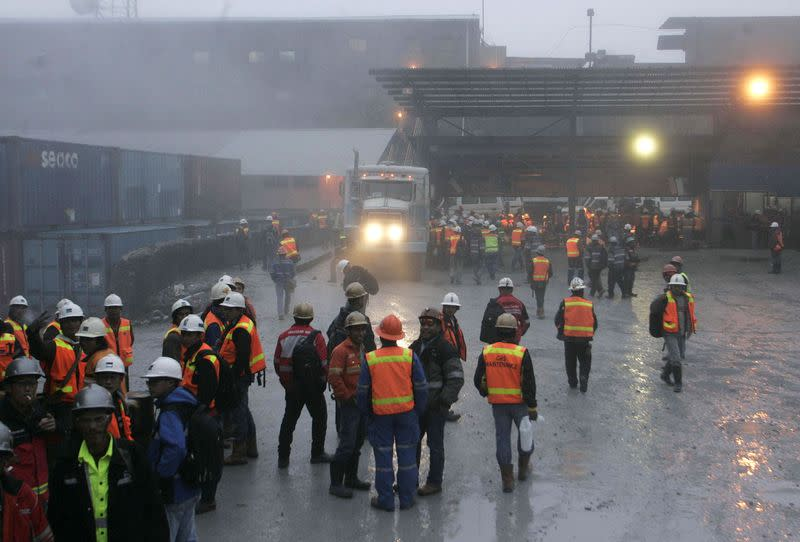 FILE PHOTO: Freeport workers gather around security gate at at Grasberg mine area in Tembagapura