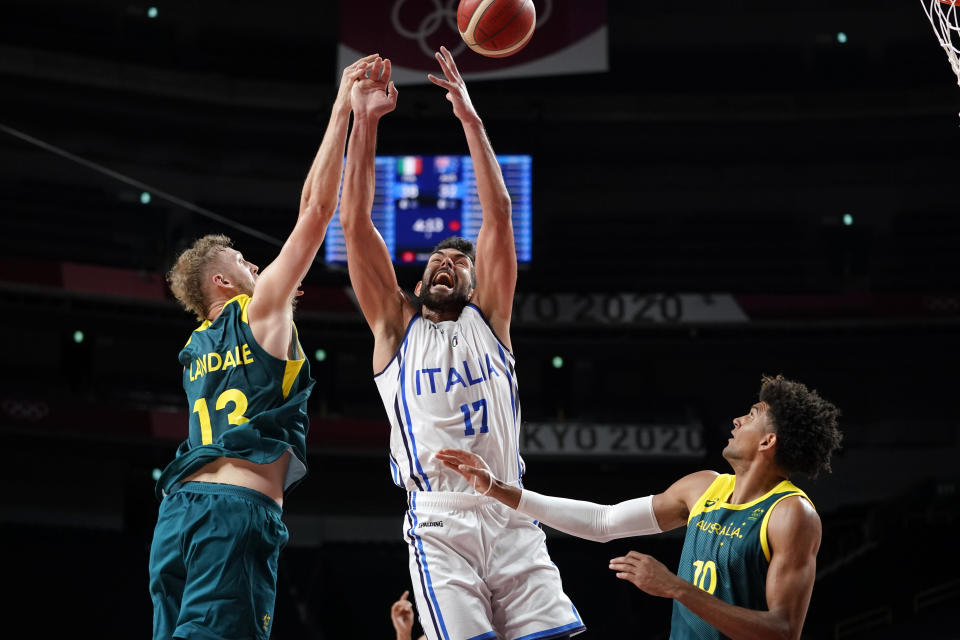 Italy's Giampaolo Ricci (17) fights for a rebound with Australia's Jock Landale (13) and Matisse Thybulle (10) during a men's basketball preliminary round game at the 2020 Summer Olympics, Wednesday, July 28, 2021, in Saitama, Japan. (AP Photo/Charlie Neibergall)