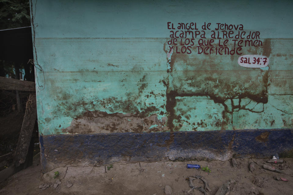 "Stains left by mud and water from last year's hurricanes Eta and Iota mark a wall decorated by a Bible passage in the Saviñon Cruz neighborhood of San Pedro Sula, Honduras, Tuesday, Jan. 12, 2021. The words say in Spanish ""The angel of the Lord encamps around those who fear him, and he delivers them. Psalm 34:7"" (AP Photo/Moises Castillo)"