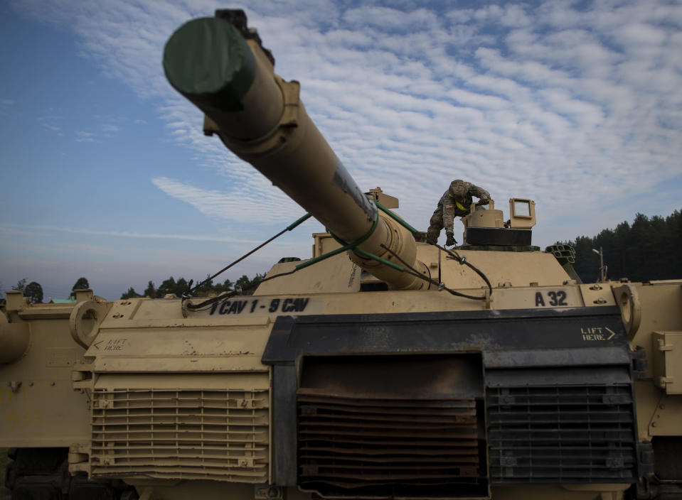 FILE - In this Oct. 21, 2019, file photo a member of the US Army's 1st Armored Battalion of the 9th Regiment, 1st Division from Fort Hood in Texas prepare to unload Abrams battle tanks from rail cars as they arrive at the Pabrade railway station some 50 km (31 miles) north of the capital Vilnius, Lithuania. (AP Photo/Mindaugas Kulbis, File)