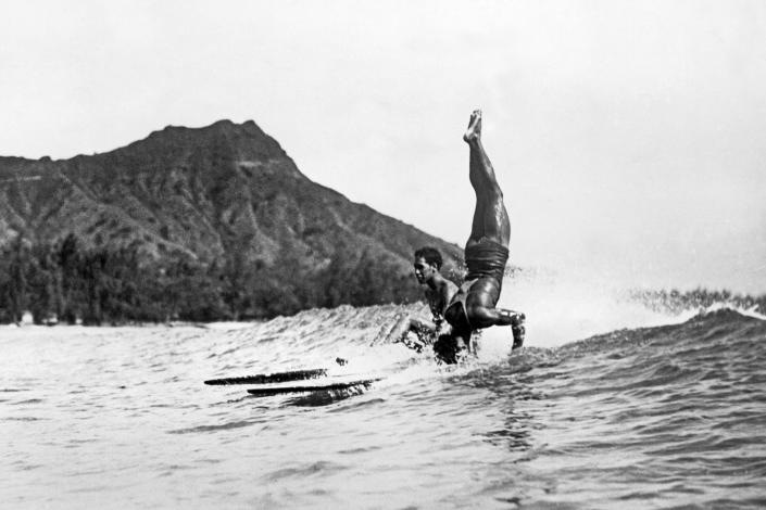 Image: A surfer at Waikiki Beach stands on his head as he rides a wave into the shore in Honolulu c. 1925. (Underwood Archives / Getty Images)