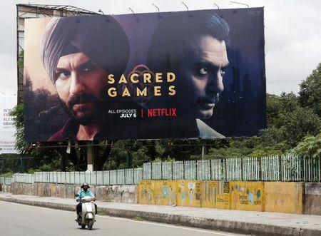"A man rides his scooter past a hoardings of Netflix's new television series ""Sacred Games"" in Bengaluru, India, July 11,  2018.  REUTERS/Abhishek N. Chinnappa"