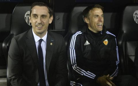 Valencia's British coach Gary Neville (L) and brother and assistant coach Philp Neville smile from the sidelines - Credit: JOSE JORDAN/AFP