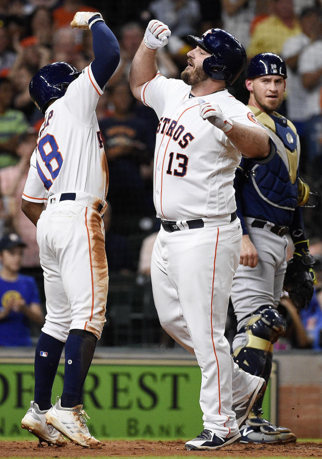 Houston Astros' Tyler White (13) celebrates his two-run home run off Milwaukee Brewers starting pitcher Freddy Peralta with Tony Kemp during the second inning of a baseball game, Tuesday, June 11, 2019, in Houston. (AP Photo/Eric Christian Smith)
