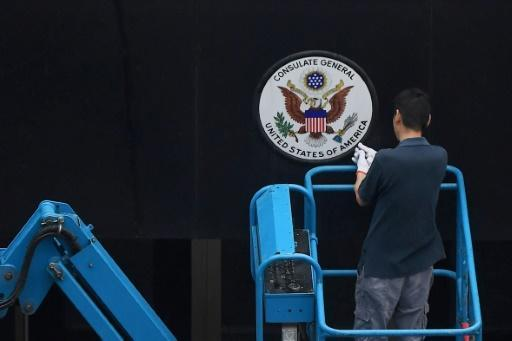 A worker removes the Great Seal of the United States from the front of the US consulate in the Chinese city of Chengdu