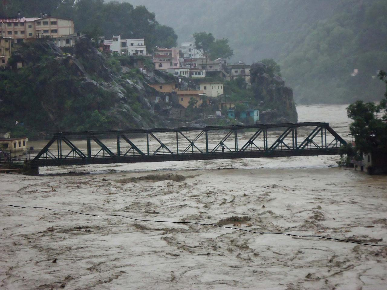RUDRAPRAYAG, INDIA - JUNE 17: Several houses on the banks of Alaknanda River have fallen prey to the rise in water level post heavy rainfall on June 17, 2013 in Rudraprayag, India. 11 people died, nearly 50 were missing and thousands stranded in landslides set off by the incessant downpour in Uttarakhand. (Photo by Badri Nautiyal/Hindustan Times via Getty Images)