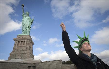 Bethany McNew, 24, from Tampa, mimics the pose of the Statue of Liberty as she poses for a photo on Liberty Island in New York, October 13, 2013. REUTERS/Carlo Allegri