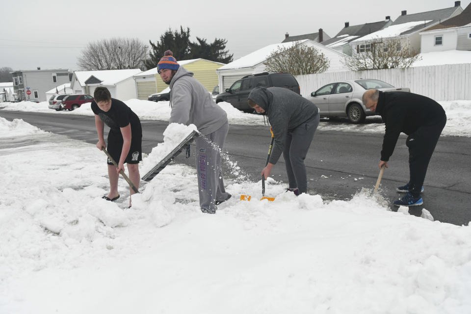 From left, George Shimko III, Devan Shimko, Hunter Shimko, and their father George Shimko Jr., shovel out a parking spot in Frackville, Pa., on Monday, Feb. 15, 2021. (Jacqueline Dormer/Republican-Herald via AP)