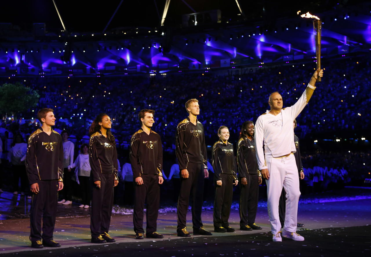 Steve Redgrave, right, holds the Olympic torch after entering the stadium during the Opening Ceremony at the 2012 Summer Olympics, Saturday, July 28, 2012, in London. (AP Photo/Matt Dunham, Pool)