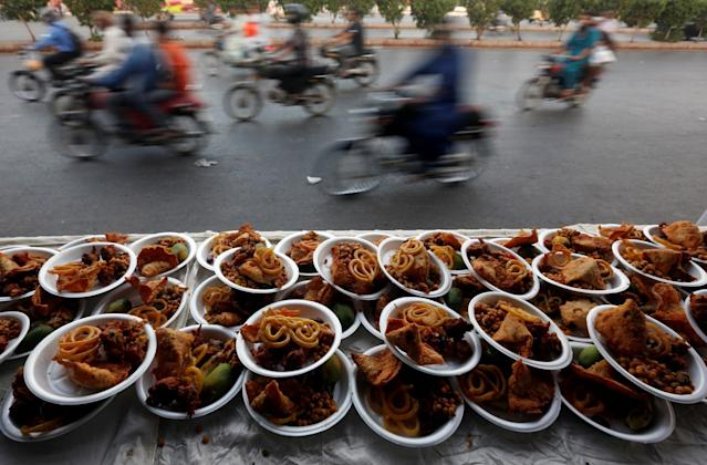 <p>Commuters travel past plates of food placed for passersby to break their fast during Ramadan in Karachi, Pakistan, May 29, 2017. (Akhtar Soomro/Reuters) </p>