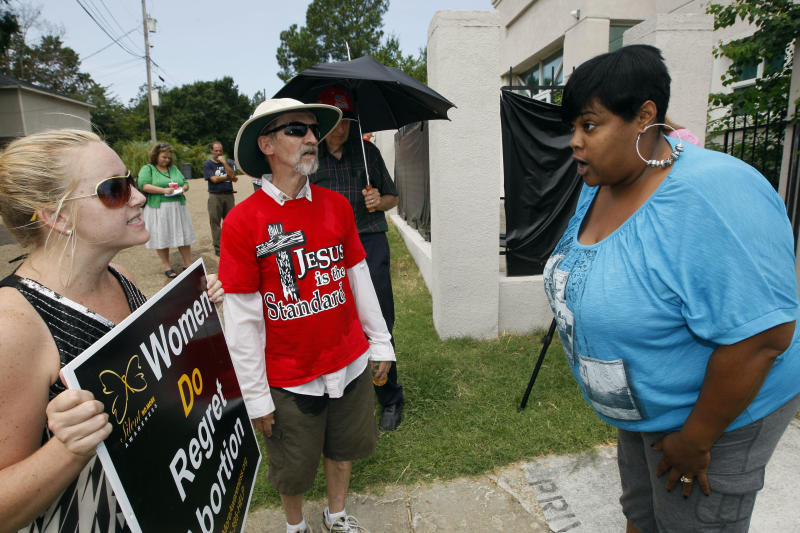 FILE- In this Monday, July 2, 2012, file photo, abortion opponents Ron Nederhoed, center, and Ashley Sigrest, left, argue with Jackson Women's Health Organization's administrator Shannon Brewer, right, over the opponent's trespassing onto the property of Mississippi's only abortion clinic in Jackson, Miss. Restricting abortion has long been a conservative goal in Mississippi, and now, a Republican-appointed federal judge is considering the constitutionality of the state's stringent new abortion law. (AP Photo/Rogelio V. Solis, File)