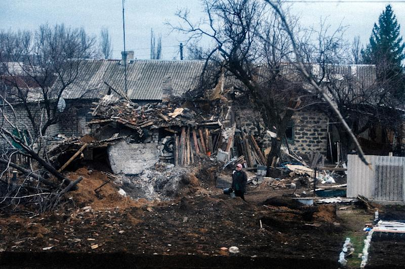 A woman, seen through a train window, stands in front of her destroyed house in the town of Vuhlehirsk, Ukraine, on March 28, 2015 (AFP Photo/Dimitar Dilkoff)