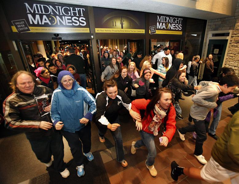 FILE -In this Friday, Nov. 23, 2012, file photo, Black Friday shoppers pour into the Valley River Center mall for the Midnight Madness sale, in Eugene, Ore. U.S. shoppers hit stores and websites at record numbers over the four-day Thanksgiving weekend, according to a survey released by the National Retail Federation on Sunday. They were attracted by retailers' efforts to make shopping easier, including opening stores on Thanksgiving evening, updating mobile shopping applications for smartphones and tablets, and expanding shipping and layaway options. (AP Photo/The Register-Guard, Brian Davies)
