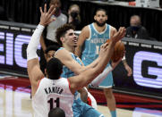 Charlotte Hornets guard LaMelo Ball, center, drives to the basket on Portland Trail Blazers center Enes Kanter, right, during the first half of an NBA basketball game in Portland, Ore., Monday, March 1, 2021. (AP Photo/Steve Dykes)