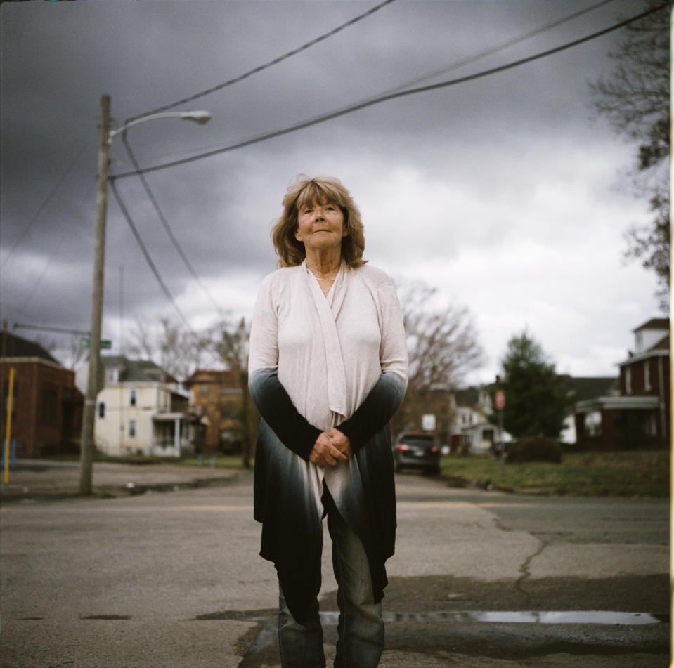 """In this photo made with a medium format film camera, Sue Howland, a member of the Quick Response Team that tries to track down everyone who overdoses to offer help, stands for a portrait in Huntington, W.Va., Thursday, March 18, 2021. The 62-year-old peer recovery coach nearly drank herself to death years ago, so she can relate to the madness her clients are facing. """"We're going to love them until they learn to love themselves. We're going to love them back to life,"""" said Howland, who's been sober now for 10 years. """"The things that bring me the greatest pleasures now are priceless: waking up in the morning, the sunrise, being able to walk on a beach, hearing the birds sing, seeing a rainbow, seeing raindrops fall in puddles, seeing somebody smile. I tell people when they come into treatment, I say you're giving yourself a gift money can't buy."""" (AP Photo/David Goldman)"""