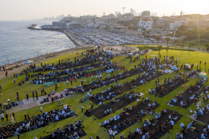 Muslim worshippers offer Eid al-Adha prayer at a park as mosques are limited for ten people following the government's measures to help stop the spread of the coronavirus, in the mixed Arab Jewish city of Jaffa, near Tel Aviv, Israel, Friday, July 31, 2020. This is the first Feast of Sacrifice since the onset of the global coronavirus pandemic. The major Muslim holiday, at the end of the hajj pilgrimage to Mecca, is observed around the world by believers and commemorates prophet Abraham's pledge to sacrifice his son as an act of obedience to God. (AP Photo/Oded Balilty)