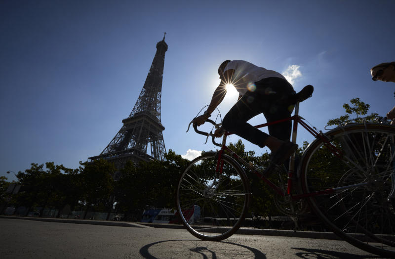 PARIS, FRANCE - AUGUST 04: A cyclist rides past the Eiffel Tower on August 04, 2020 in Paris, France. Since the end of lockdown the number of cyclists in Paris has risen by nearly 50 percent as authorities have encouraged cycling as a safer, and more environmentally friendly form of transport away from crowded buses and metro trains as they continue to try to halt the spread of COVID-19. Mayor Anne Hidalgo has added a further 31 miles of roadway in the city for bikes with the promise of making Paris a cycling capital. (Photo by Kiran Ridley/Getty Images)