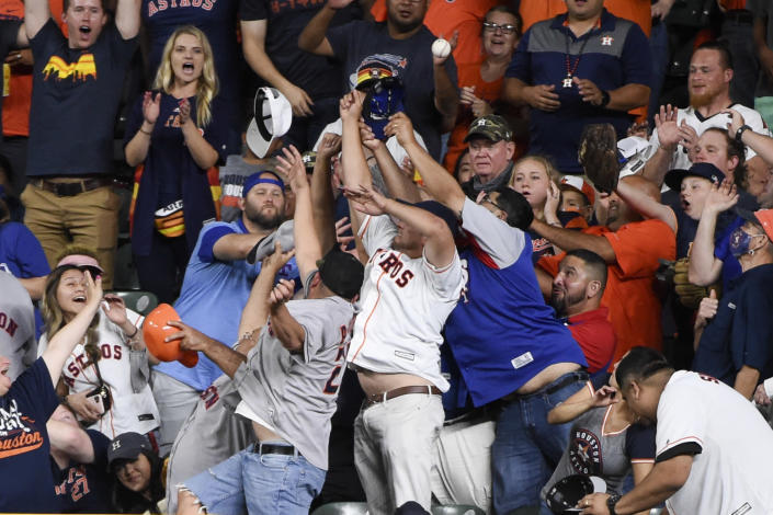 Fans try to catch the home run ball of Houston Astros' Kyle Tucker during the seventh inning of a baseball game against the Texas Rangers, Saturday, May 15, 2021, in Houston. (AP Photo/Eric Christian Smith)