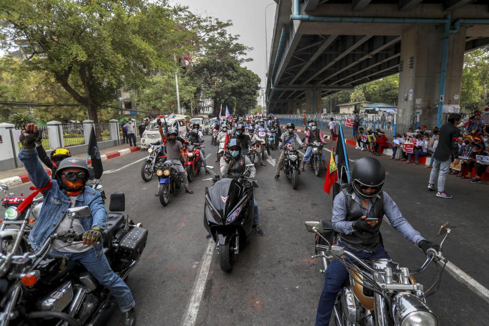 Demonstrators on motorbikes flashe the three-fingered salute during a protest against the military coup in Yangon, Myanmar Thursday, Feb. 18, 2021. Demonstrators against Myanmar's military takeover returned to the streets Thursday after a night of armed intimidation by security forces in the country's second biggest city.(AP Photo)