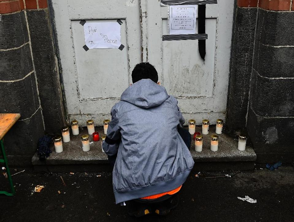 A man lights candles next to a door at the State Office of Health and Social Affairs registration centre for refugees after a volunteer claimed the death of a Syrian migrant in Berlin on January 27, 2016 (AFP Photo/Tobias Schwarz)