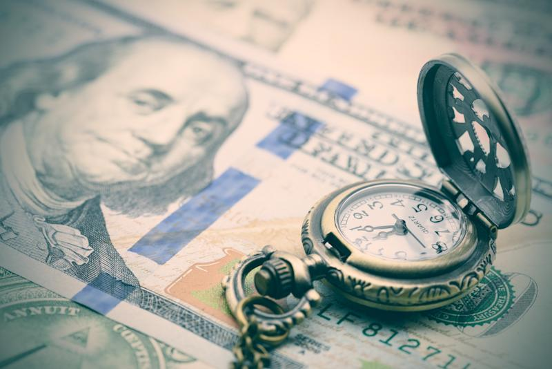 Pocket watch sitting on top of money.