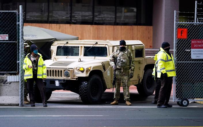 A National Guard soldier stands guard outside the courthouse - Jim Mone/AP