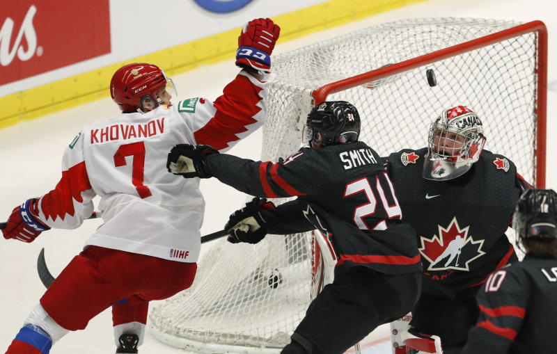 Canada's goaltender Joel Hofer, right, eyes the puck as Canada's Ty Smith, center, challenges Russia's Alexander Khovanov during the U20 Ice Hockey Worlds gold medal match between Canada and Russia in Ostrava, Czech Republic, Sunday, Jan. 5, 2020. (AP Photo/Petr David Josek)