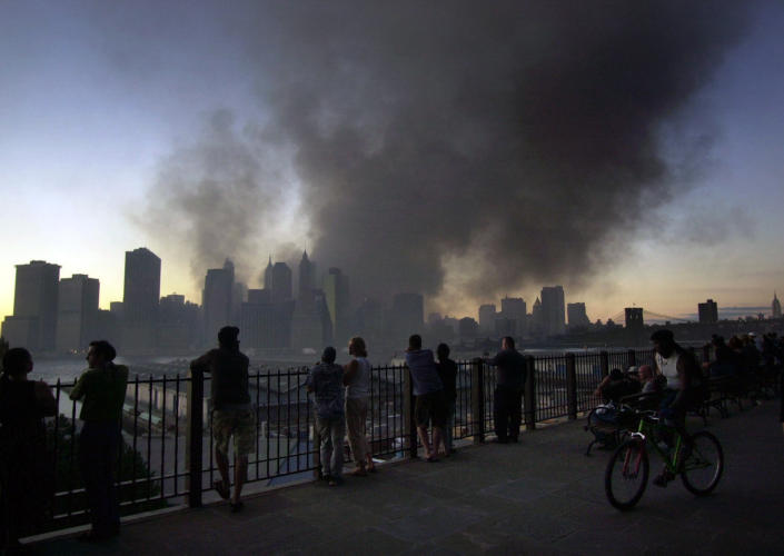<p>Pedestrians on Pierrepont Place in the Brooklyn borough of New York, watch as smoke billows from the remains of the World Trade Center in New York, Sept. 11, 2001. (AP Photo/Lawrence Jackson)</p>
