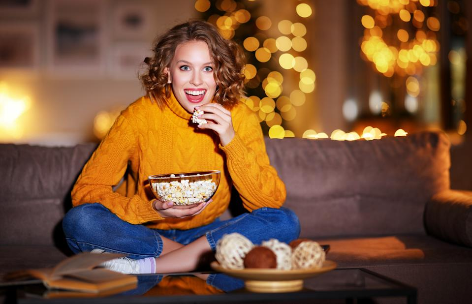 young  delighted cheerful woman eating popcorn laughs and watches  christmas comedy movie on  cable TV   at home in evening  alone