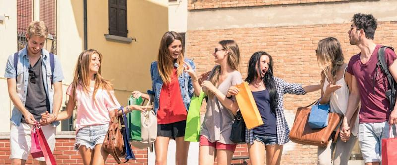 Group of happy best friends with shopping bags in the city center - Tourists walking and having fun in the summer around the old town - University students during a break in a sunny day