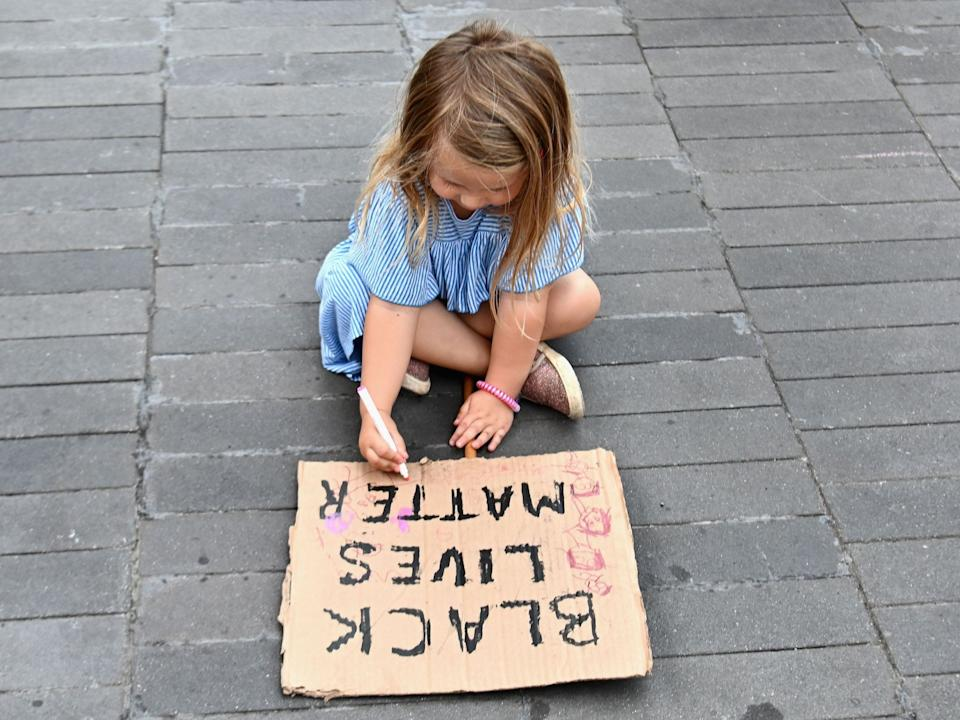 A child draws on a sign at a Black Lives Matter protest in New York.