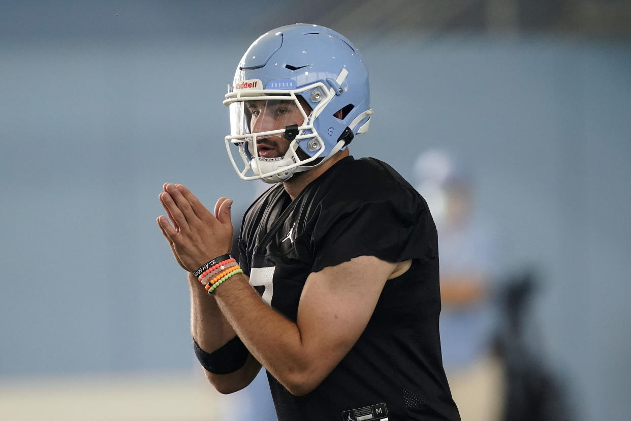 FILE - North Carolina quarterback Sam Howell takes a snap during an NCAA college football practice in Chapel Hill, N.C., in this Thursday, Aug. 5, 2021, file photo. The Tar Heels return 18 starters from an eight-win team and are picked to win the ACC's Coastal Division. (AP Photo/Gerry Broome, File)