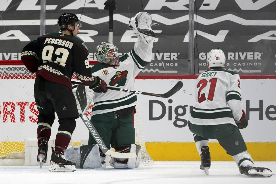 Minnesota Wild goaltender Cam Talbot reaches up to make a glove save as Arizona Coyotes center Lane Pederson (93) and Wild defenseman Carson Soucy (21) look on during the second period of an NHL hockey game Wednesday, April 21, 2021, in Glendale, Ariz. (AP Photo/Ross D. Franklin)