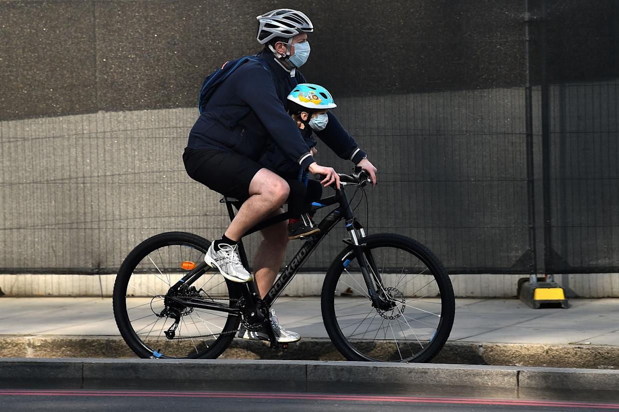 """A man, and a child, both wearing face masks as a precautionary measure against COVID-19, cycle past St Thomas' Hospital in central London on April 12, 2020, where Britain's Prime Minister Boris Johnson is recovering after contracting the novel coronavirus COVID-19. - Britain's Prime Minister Boris Johnson was making """"very good progress"""" on Saturday in his recovery in hospital from coronavirus, officials said, as the country's deaths toll from the disease approached the grim milestone of 10,000. (Photo by Glyn KIRK / AFP) (Photo by GLYN KIRK/AFP via Getty Images)"""