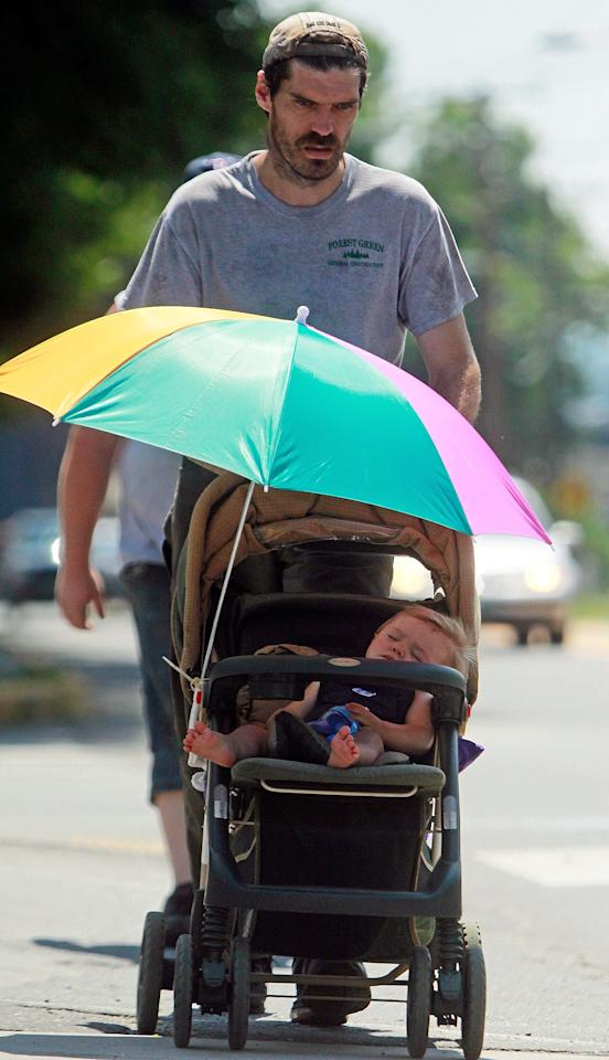 Frank Hathaway pushes his 9-month-old son, James, down the street under an umbrella in the noontime heat, Wednesday, July 17, 2013 in Barre, Vt. The heat wave continued on Wednesday in Vermont. (AP Photo/Toby Talbot)
