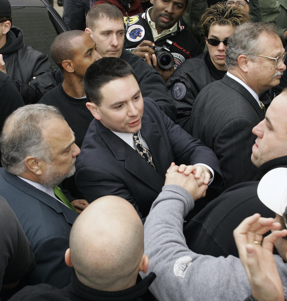 New Orleans Police Sgt. Kenneth Bowen shakes hands with a supportter as he and six other New Orleans police officers arrive at the city jail in New Orleans, Tuesday, Jan. 2, 2007. Each officer faces at least one charge of murder or attempted murder in the shootings of six people on the Danzinger Bridge during Hurricane Katrina.  (AP Photo/Chuck Burton)