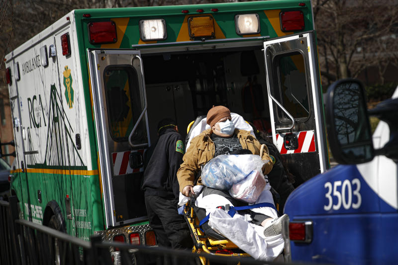A patient wears a protective face mask as she is loaded into an ambulance at The Brooklyn Hospital Center emergency room, Wednesday, March 18, 2020, in New York. Anticipating a spike in coronavirus patients, New York City-area hospitals are clearing out beds, setting up new spaces to triage patients and urging people with mild symptoms to consult health professionals by phone or video chat instead of flooding emergency rooms that could be overrun. (AP Photo/John Minchillo)