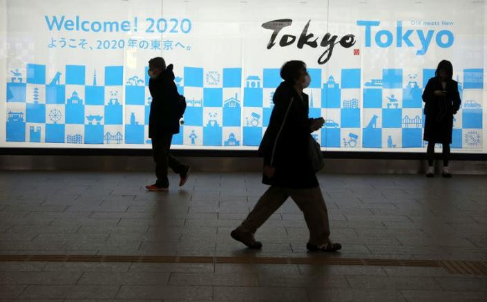 Man wearing a protective mask in front of an advertising billboard of Tokyo Olympics 2020, near the Shinjuku station in Tokyo