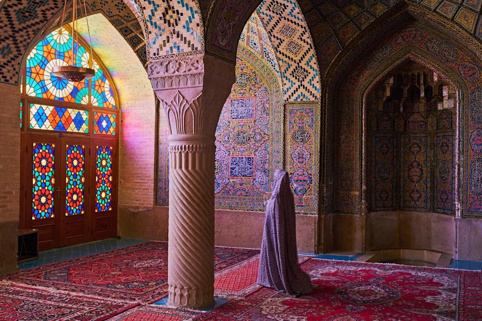 """Also known as """"The Pink Mosque,"""" Nasir al-Mulk Mosque in Shiraz, <a href=""""https://www.cntraveler.com/stories/2016-01-22/is-iran-ready-for-western-tourists?mbid=synd_yahoo_rss"""" rel=""""nofollow noopener"""" target=""""_blank"""" data-ylk=""""slk:Iran"""" class=""""link rapid-noclick-resp"""">Iran</a>, is famous for its stunning array of colors—thanks to a unique combination of stained glass windows and mosaics. When Nasir al-Mulk was built in 1888, it was specially designed to take advantage of morning light, and the sun filtering through the windows creates a rainbow effect, highlighting the jewel-toned tiles and rugs in the interior. If you're able to visit the mosque, make sure you go early for the best view."""